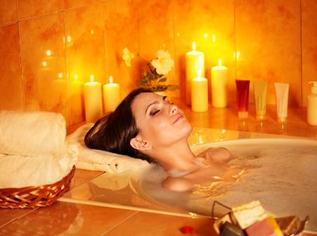 baÑo: Mujer joven tomar un baño de burbujas con velas.