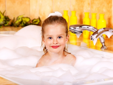 Little girl washing in bubble bath . photo