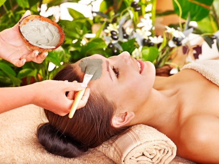 Woman with clay facial mask in beauty spa. Stock Photo