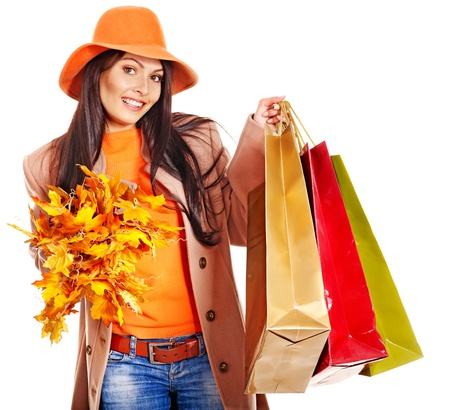 overcoat: Woman wearing autumn overcoat and hat holding shopping bag.