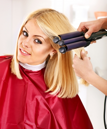peluqueria: Mujer en el peluquero con rizador de pelo de hierro.