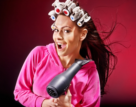 hairdryer: Happy woman wear hair curlers holding  hairdryer.