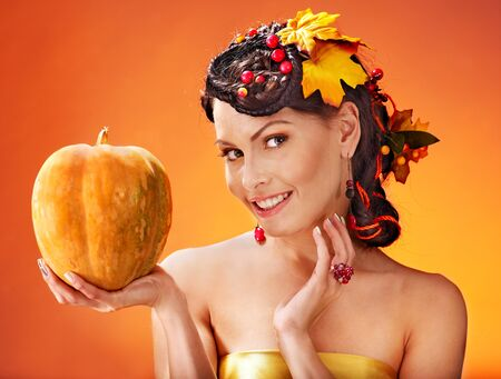Woman holding autumn pumpkin and leaves. photo
