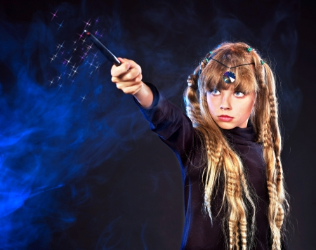 Girl  holding magic wand casting spells. photo