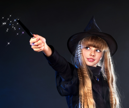 Girl in witch's hat with magic wand casting spells. photo
