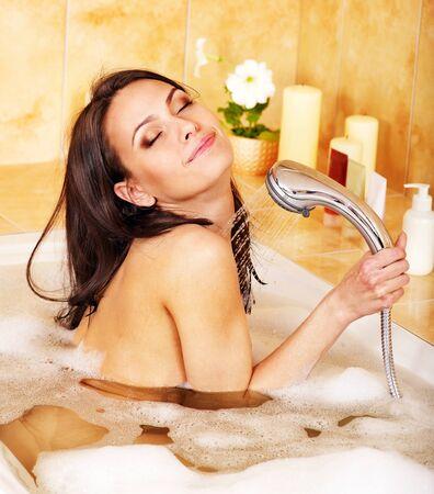 llave de agua: Feliz mujer joven tomar un baño de burbujas.