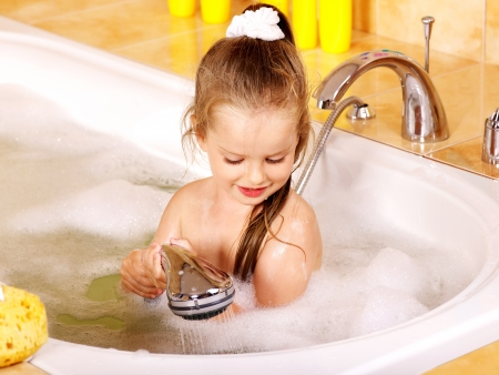 Child washing in bubble bath . Stock Photo