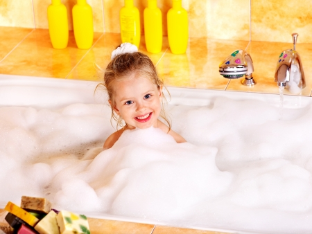steam bath: Happy little girl washing in bubble bath .