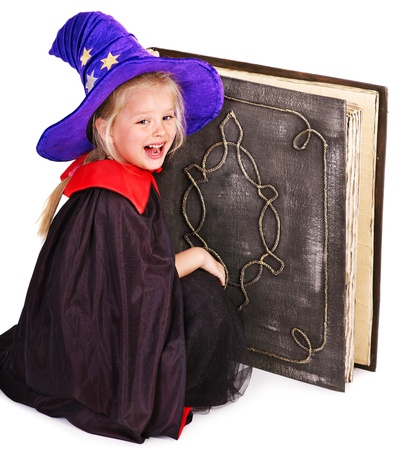 Witch little girl holding old Halloween book. . Stock Photo - 15635306
