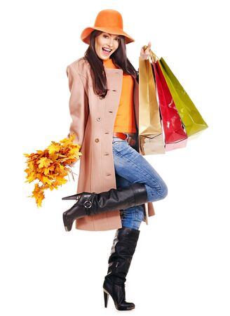 Woman wearing autumn overcoat and hat holding shopping bag. photo
