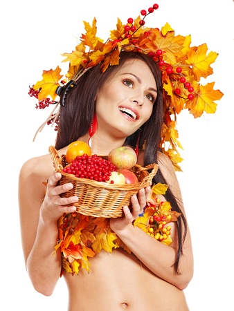 Girl with wreath of autumn leaves holding basket with fruit. photo