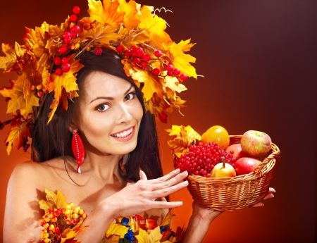 Girl with wreath of autumn leaves holding basket with fruit. Stock Photo - 15635030