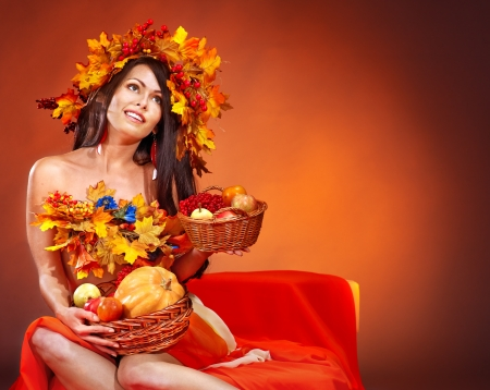 Girl with wreath of autumn leaves holding basket with fruit. Stock Photo - 15634998