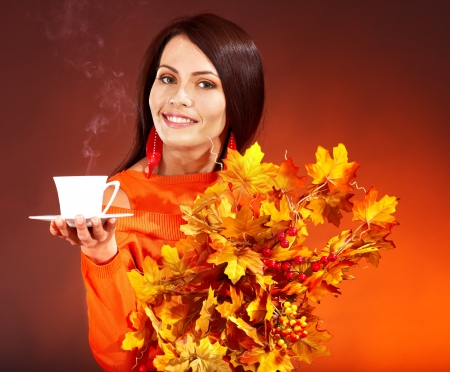 Woman holding  cup of coffee and orange leaves. photo