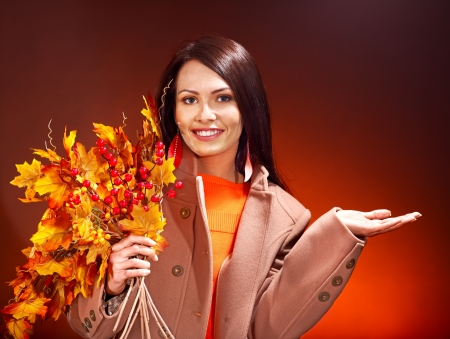 Woman wearing overcoat holding  orange leaves. Stock Photo - 15635194