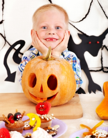 Halloween party with child holding carved pumpkin. photo