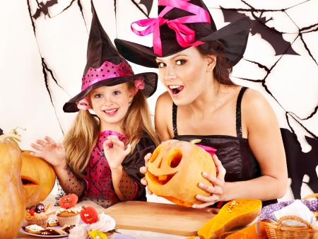 halloween kids: Mother and daughter on Halloween party with  carved pumpkin.