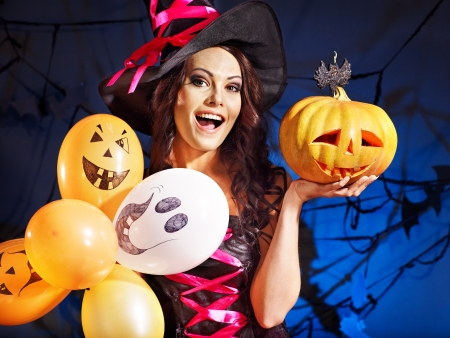 pumkin: Happy witch woman holding pumkin and balloon. Stock Photo