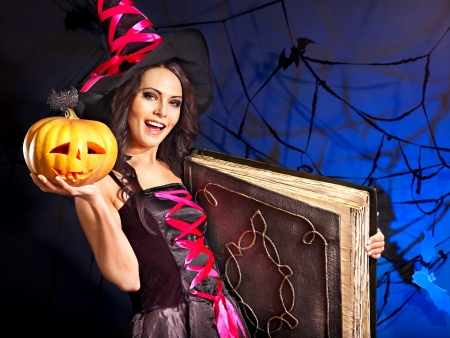 Happy witch woman holding old book and pumkin. Stock Photo - 15635283