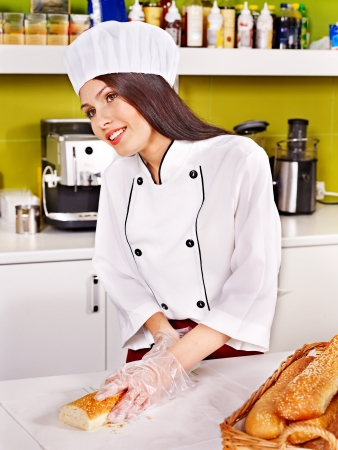 Female chef baking baguette bread photo