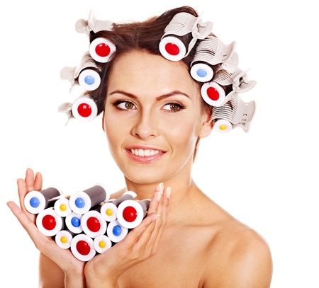 Happy beautiful woman wear hair curlers on head. photo
