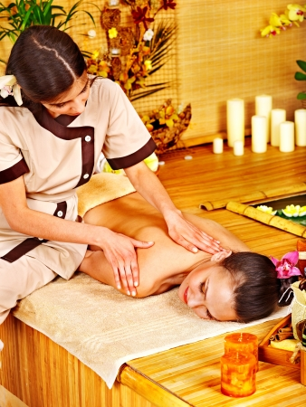 beauty parlour: Young woman getting massage in bamboo spa.