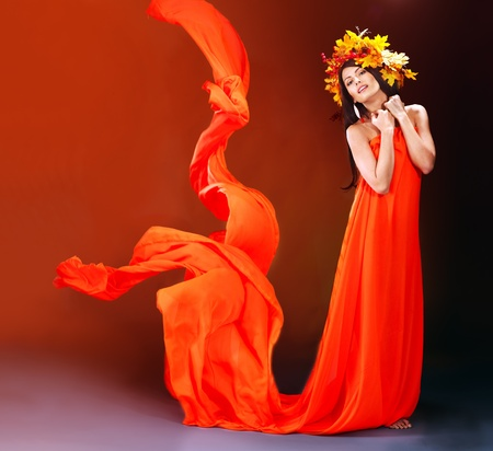 Girl with wreath of autumn leaves and orange dress.  photo