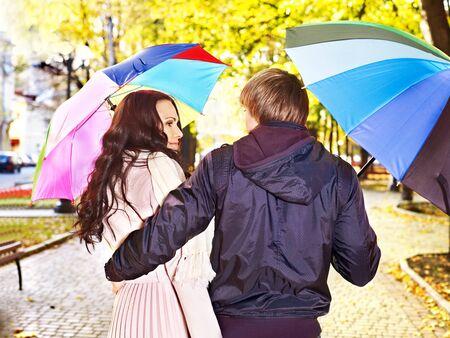 yellow umbrella: Couple holding umbrella  autumn outdoor. Rear view.