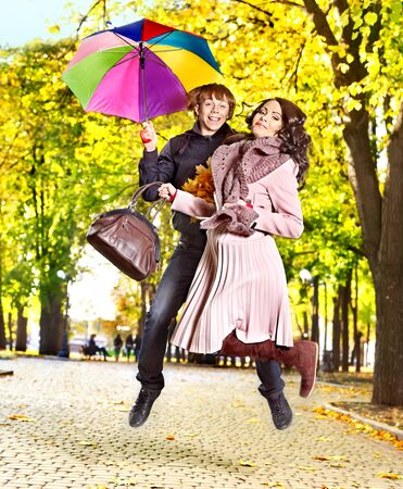 Couple holding umbrella  autumn outdoor. Stock Photo - 15832414
