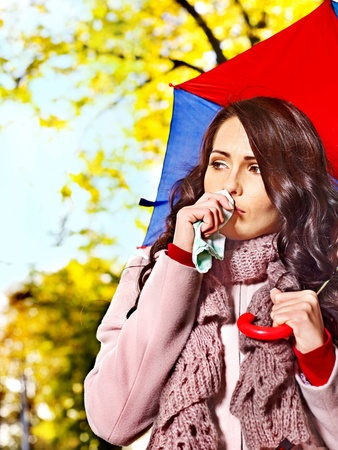hankie: Woman sneezing handkerchief fall outdoor.