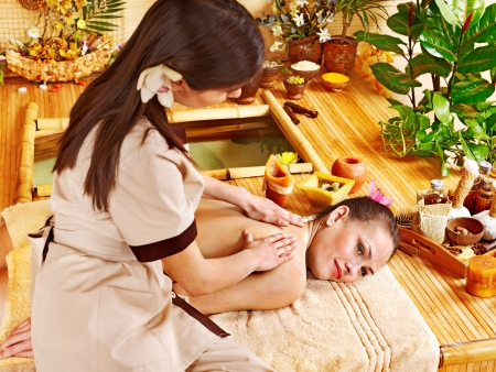 massage herbal: Young woman getting massage in bamboo spa.