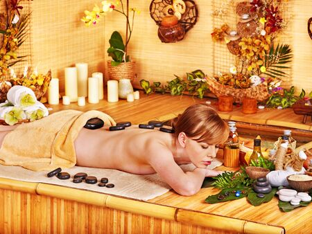 stone bowl: Woman getting stone therapy massage in bamboo spa.