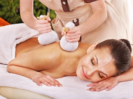massage oil: Woman getting herbal ball massage treatments  in spa.