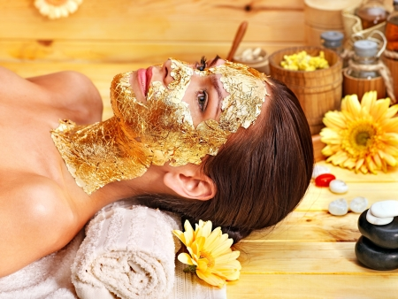 body mask: Woman getting  gold facial mask.