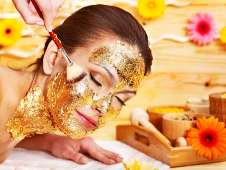 white mask: Woman getting  gold facial mask.