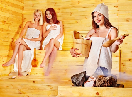 Women pouring water on rock in sauna. photo