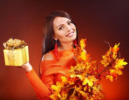 Woman holding gold gift box . Autumn season. photo