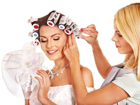 hair styling: Woman with hair curlers on head wear in wedding dress . Stock Photo