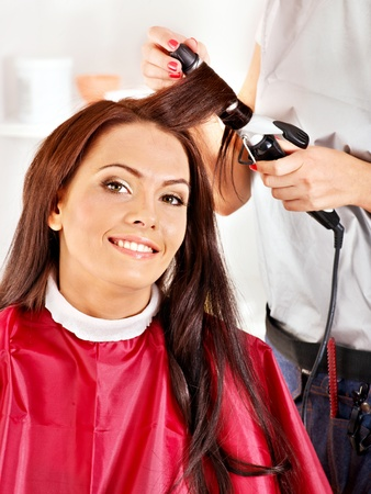 curling irons: Woman at hairdresser with iron hair curler.