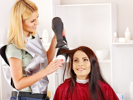 Woman at hairdresser with hairdryer. photo