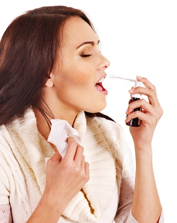 Young woman using throat spray. Isolated. photo