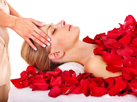 Woman getting facial  massage in rose petal spa. Isolated. photo