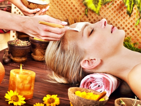 parlour: White woman getting facial mask in tropical beauty spa.