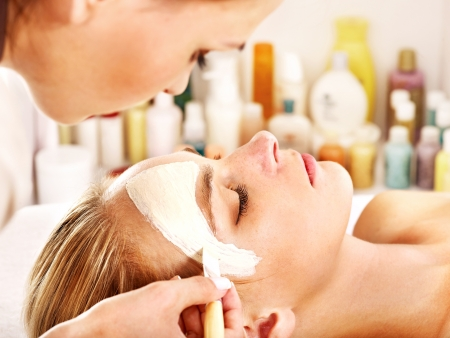 cosmetician: White woman getting facial mask in tropical beauty spa.