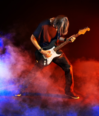 lighting effects musician: Man playing  guitar in night club. Lighting effects. Stock Photo