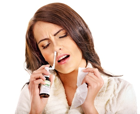 angina: Young woman using throat spray. Isolated.