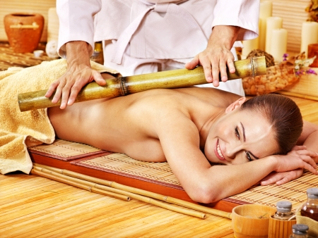 bamboo therapy: Young woman getting bamboo massage. Male therapist.
