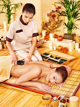 bamboo therapy: Woman getting stone therapy massage in bamboo spa.