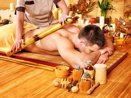 Man getting bamboo massage. Female therapist. photo