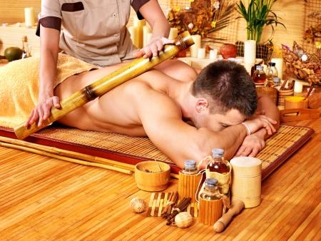 female therapist: Man getting bamboo massage. Female therapist. Stock Photo